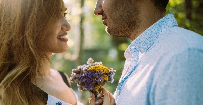 Happy Couple Holding Wildflowers