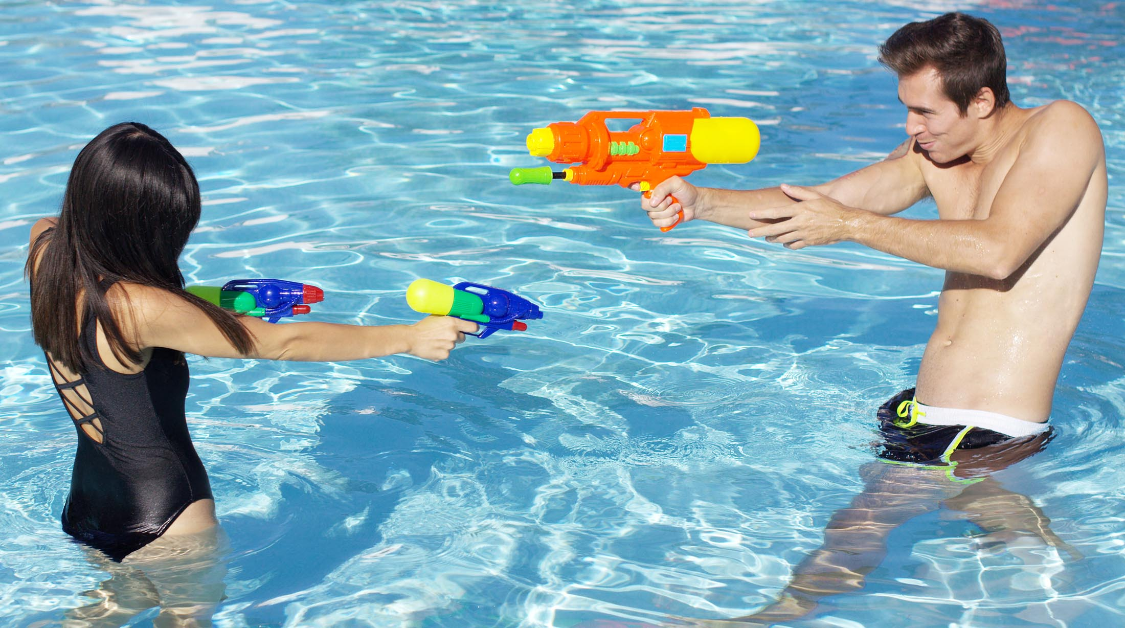 Playful Couple Battling in Pool with Water and Nerf Guns